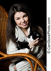 The girl with a cat in an armchair
