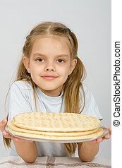 The girl with a slight smile holding a pizza crust on a plate