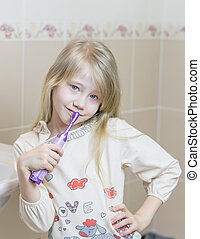 The girl with an electric toothbrush in the bathroom.