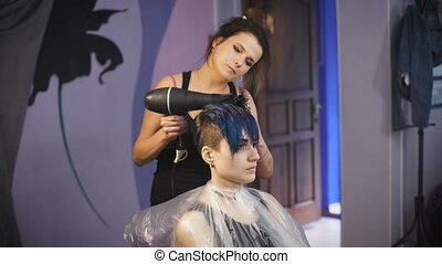 The girl with blue hair in a beauty salon. Hairdresser makes...
