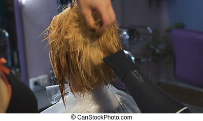 The girl with bright red hair in a beauty salon.