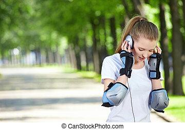 The girl with ear-phones against green trees