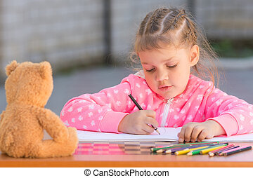 The girl with enthusiasm draws with crayons in the album