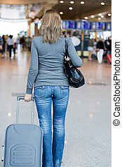 The girl with luggage at the airport