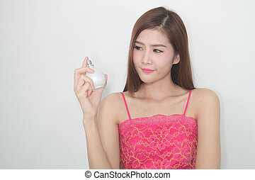 The Girl with perfume, young beautiful woman holding bottle of perfume and smelling aroma,