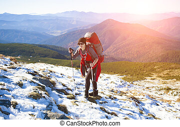 The girl with the backpack goes to the mountain top.