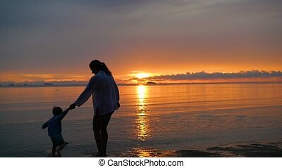 the girl with the child go for walks and play on the beach at sunset time