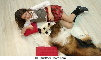 The girl with the dog is lying on the floor.