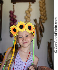 The girl with the floral decoration on the head in a village house.