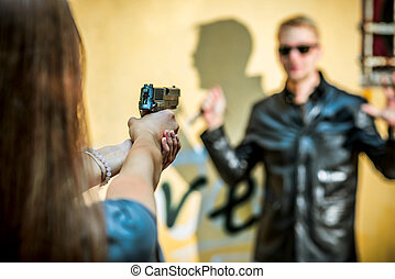 the girl with the gun holds on the sight of a batcher whose knife is in her hand. A cold-robed thug wants to attack a woman