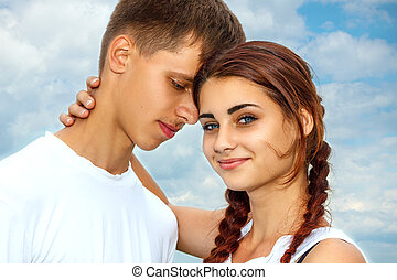 the girl with the guy standing in hugging each other on the sky background