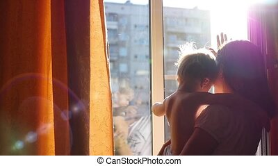 the girl with the kid gently cuddling in the sun slowmotion