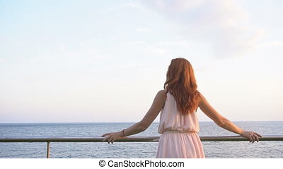 the girl with the red hair looks into the ocean 1