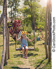 The girl with the sunflowers on her head is swinging on a swing in the village in summer day.