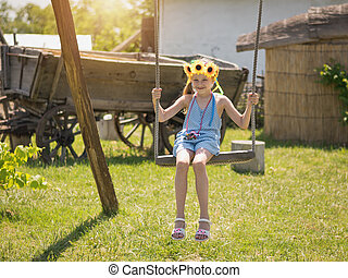 The girl with the sunflowers on her head is swinging on a vintage swing in the village in summer day.