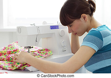 The girl works at sewing machine
