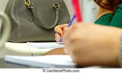 The girl writes a lecture in a notebook. - bored at the...