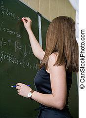 The girl writes chalk on a blackboard