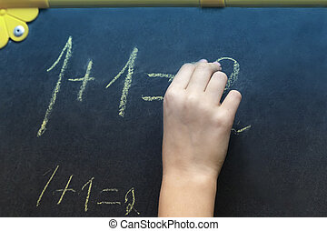 The girl writes in chalk on the blackboard.