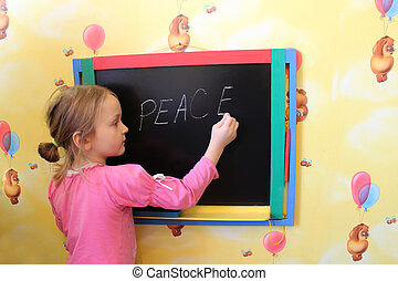 The girl writes on a blackboard a word the peace