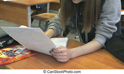 The girl writes the text in a notebook indoors