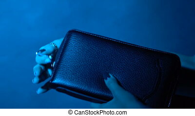 The girl zips the wallet - The girl closes the zipper purse....