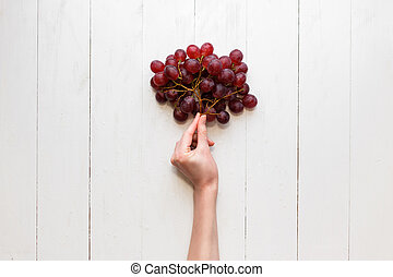 The girl's hand holds on to a bunch of red grapes on a wooden background. View from above. Grapes are like balloons.
