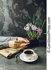 The girl's hands closeup with a pen in hand writing in a notebook. On the table is a Cup of coffee and a vase with flowers crocuses