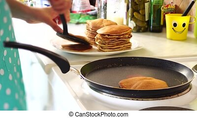 The girl's hands in a blue apron are removed from the pan of the pancake with a spatula. Puts the pancakes in a pile. High quality 4k footage