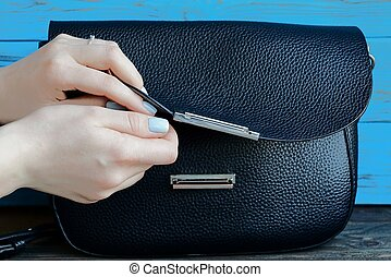 The girl's hands open a black leather bag