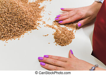 The girls in the kitchen take away the rice from the dirt. Purification of brown rice from husks
