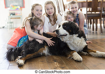 girls on the floor with the Bernese Mountain Dog