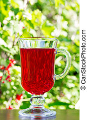 the glass with dark red cherry juice on natural green background closeup