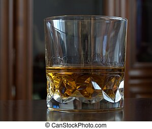 The glass with whisky on table