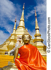 The Gloden Seated Buddha Image in Attitude of Meditation and Golden Pagoda with Cloudy Blue Sky.