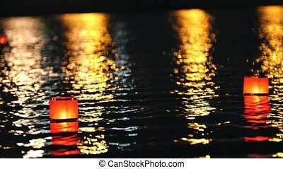 The glowing lanterns on a city river at night - romantic festival