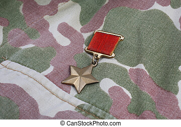 """The Gold Star medal is a special insignia that identifies recipients of the title """"Hero"""" in the Soviet Union on Soviet camouflage uniform background"""