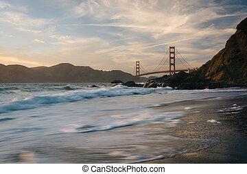 The Golden Gate Bridge at sunset, seen from Baker Beach, San Francisco, California.