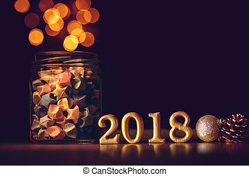 The Golden Number 2018 placed with Star origami in glass jar and festival light on dark elegant glamour night tone background for new year 2018 celebration concept