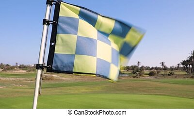 The Golf flag flies in the wind on a Sunny day