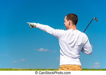the golfer shows his hand the trajectory of the flight of...