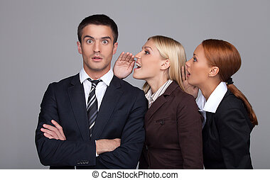 The gossip line. Two beautiful young businesswoman telling gossips to the businessman