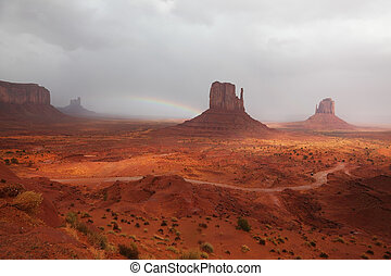 "The grand landscape of Monument Valley. Famous ""Mittens"" of red sandstone in a fog after the storm and a rainbow in the sky"