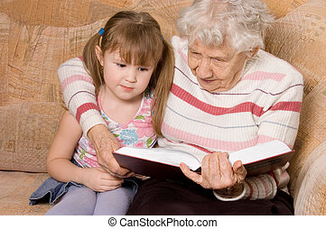 The grandmother with the grand daughter read the book