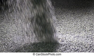 The granular cement crumb pours , slow motion ,