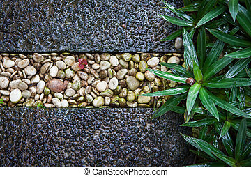 The grass next to the pavement of flint stones of various colors