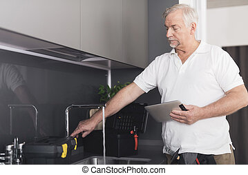 The gray plumber stands in the kitchen next to the tap. He checks the work of crane and holds a gray tablet in his hands
