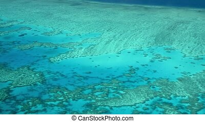 The Great Barrier Reef as seen from the airplane. Beautiful ocean colors, aerial view. Slow motion.