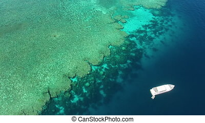 An aerial shot of the great barrier reef. A white small ship can be seen in the middle of the blue ocean.