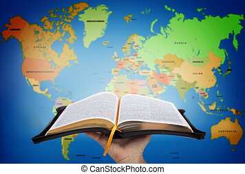 Hand showing the Holy Bible against world map